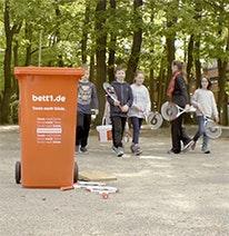 Na zdjęciu: na pierwszym planie czerwony kosz, w tle dzieci z rakietami tenisowymi.