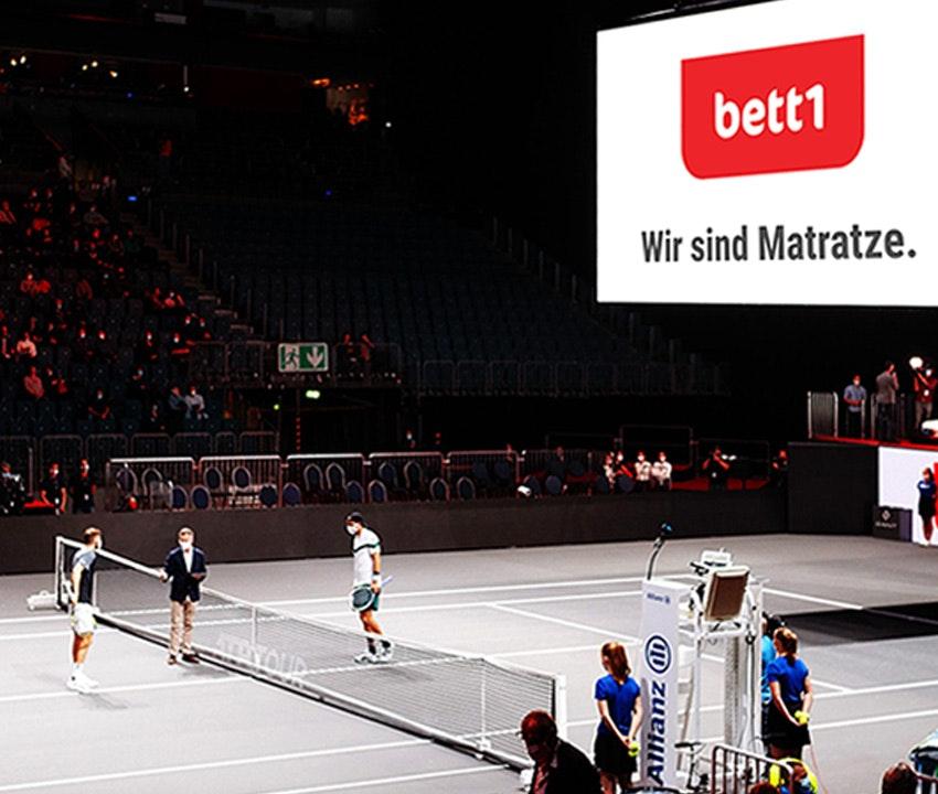 Zdjęcie: W bett1HULKS dwaj gracze stają naprzeciw siebie przy siatce, na podświetlanej tablicy na arenie widnieje hasło bett