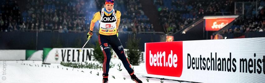 Zdjęcie: Kobieta uprawiająca narciarstwo biegowe; w tle reklama obwodowa bett1.