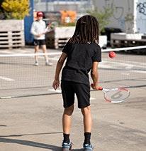 Zdjęcie: Dziecko gra czerwoną piłeczką tenisową nad siatką do innego dziecka.